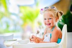 A menina de sorriso pequena tem um pequeno almoço Imagem de Stock