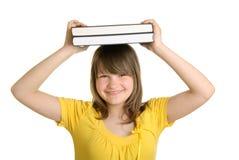A menina de sorriso prende livros na cabeça Fotografia de Stock Royalty Free