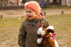 A menina de sorriso prende o cão Imagens de Stock