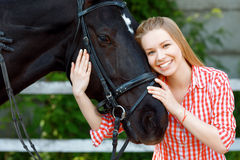 Menina de sorriso que abraça o cavalo fotografia de stock