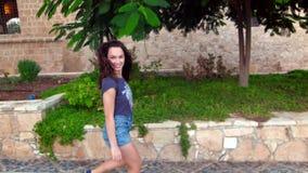 Menina de sorriso que anda ao longo da rua no movimento lento Caminhada moreno da mulher na cidade vídeos de arquivo