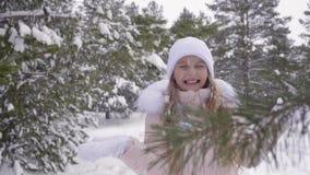Menina de sorriso que aprecia a queda de neve do inverno no tempo nevado no movimento lento da floresta video estoque