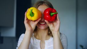 A menina de sorriso que cobre seus olhos com a paprika salpica Conceito vegetal da dieta vídeos de arquivo
