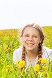 Menina de sorriso que coloca no prado dos dentes-de-leão foto de stock royalty free