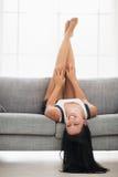 Menina de sorriso que coloca upside-down no sofá na sala imagem de stock