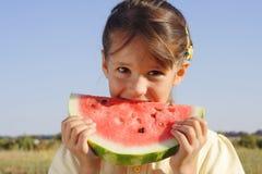 Menina de sorriso que come a melancia Imagem de Stock
