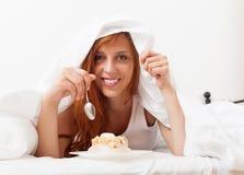 Menina de sorriso que come o biscoito na cama Fotos de Stock Royalty Free