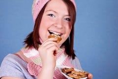 Menina de sorriso que come um bolinho imagem de stock royalty free