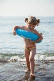 Menina de sorriso que corre para fora na água Imagens de Stock