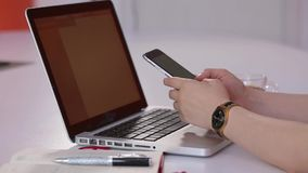 Menina de sorriso que datilografa no dispositivo esperto no escritório na frente do portátil filme