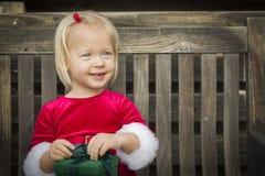 Menina de sorriso que desempacota seu presente em um banco imagem de stock royalty free
