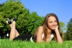 Menina de sorriso que encontra-se ao ar livre na grama Imagens de Stock