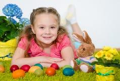 Menina de sorriso que encontra-se com ovos da páscoa e flores no verde Imagem de Stock Royalty Free