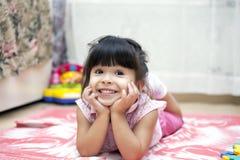 Menina de sorriso que encontra-se em uma cobertura imagem de stock