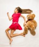 Menina de sorriso que encontra-se no assoalho e que finge correr rapidamente com ted foto de stock