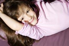 Menina de sorriso que encontra-se no sofá Imagem de Stock
