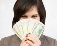 Menina de sorriso que esconde atrás de um fã dos dólares Imagens de Stock Royalty Free