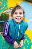 Menina de sorriso que espreita fora da janela no Fotografia de Stock Royalty Free
