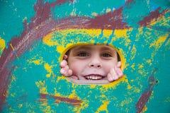 Menina de sorriso que espreita fora da janela no Imagens de Stock