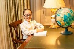 Menina de sorriso que faz trabalhos de casa na mesa clássica Fotos de Stock Royalty Free