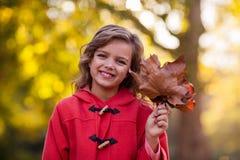 Menina de sorriso que guarda as folhas de outono no parque Imagem de Stock Royalty Free