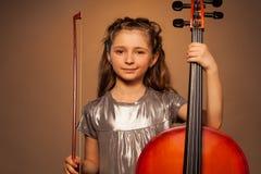 Menina de sorriso que guarda a corda para jogar o violoncelo fotografia de stock royalty free