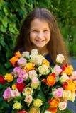 Menina de sorriso que guarda o ramalhete grande das rosas nas mãos fotografia de stock royalty free