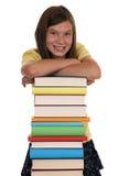 Menina de sorriso que guarda sua cabeça em livros Foto de Stock Royalty Free