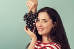 A menina de sorriso que guarda uvas aproxima sua cara e sorriso amplamente ao visor Imagem de Stock