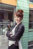 Menina de sorriso que inclina a para trás contra trilhos Fotografia de Stock