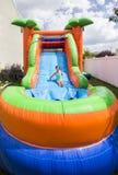 A menina de sorriso que joga em uma corrediça inflável salta a casa fora Fotos de Stock Royalty Free