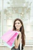 Menina de sorriso que leva muitos sacos de compras em uma rua da cidade imagem de stock
