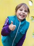 Menina de sorriso que mostra está bem fora da janela no Imagens de Stock Royalty Free