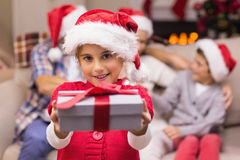 Menina de sorriso que oferece um presente com seus pais atrás Foto de Stock Royalty Free