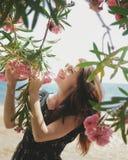 Menina de sorriso que olha acima entre as flores cor-de-rosa fotografia de stock royalty free