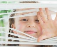 Menina de sorriso que olha através das cortinas Fotos de Stock Royalty Free