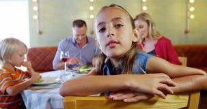 Menina de sorriso que olha a câmera quando família que come o alimento no fundo 4k vídeos de arquivo