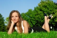 Menina de sorriso que relaxa ao ar livre na grama Fotos de Stock