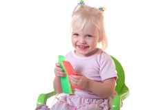 Menina de sorriso que senta-se com pentes Fotos de Stock