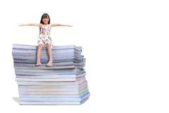 Menina de sorriso que senta-se em um livro Imagem de Stock Royalty Free