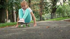 Menina de sorriso que senta-se em um skate e que empurra afastado com mãos vídeos de arquivo