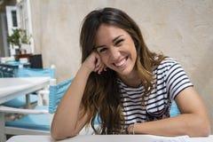 Menina de sorriso que senta-se em um terraço foto de stock