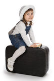 Menina de sorriso que senta-se em uma mala de viagem Imagem de Stock