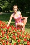 Menina de sorriso que senta-se entre flores Fotografia de Stock Royalty Free