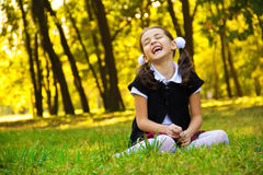 Menina de sorriso que senta-se na grama Imagem de Stock