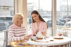 Menina de sorriso que tem o almoço com sua avó Imagens de Stock Royalty Free