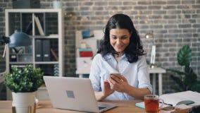 Menina de sorriso que usa o índice de observação do smartphone na tela no local de trabalho vídeos de arquivo