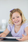 Menina de sorriso que usa o tablet pc na tabela Imagem de Stock Royalty Free