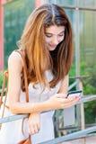 Menina de sorriso que usa seu telefone celular Imagem de Stock Royalty Free