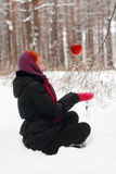 A menina de sorriso senta-se na neve e olha-se a maçã de suspensão Fotos de Stock